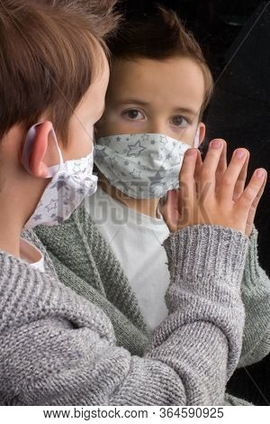Boy Medical Face Mask , Looks In The Mirror, Putting His Hand On Him. The Concept Of Isolation A Dur