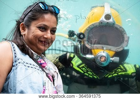 MAY 24 2019-NEW YORK: A woman poses for a picture with a US Navy EOD technician underwater in a 6,800 gallon mobile dive tank at the Military Island Plaza in Times Square, Fleet Week on May 24, 2019.