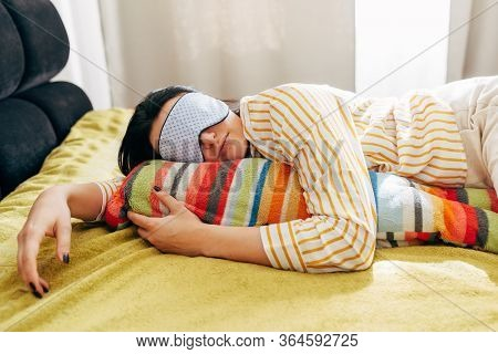Image Of Sleeping Young Woman Lying On The Bed With Sleeping Mask, Having Sweet Dreams. Female Lying