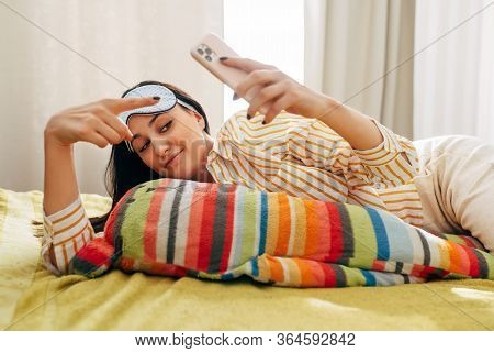 Attractive Young Woman Lying On The Bed With Sleep Mask, Looking To Mobile Phone Taking Selfie. Awak