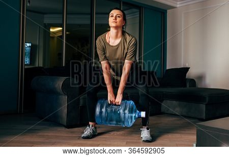 Full Body Image Of Fit Young Woman Exercising At Home With Big Bottle Of Water In The Room. Female P