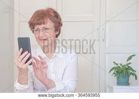 Senior Woman Using Mobile Phone At Home. Happy Retired Person Shopping Online. People Connection, Vi