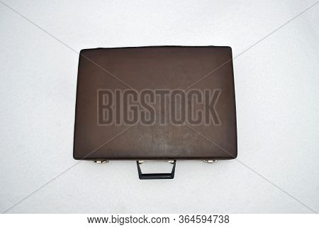 A Closed Brown Briefcase Is Lying On The Snow. On A White Background Is A Briefcase. Top View Of The