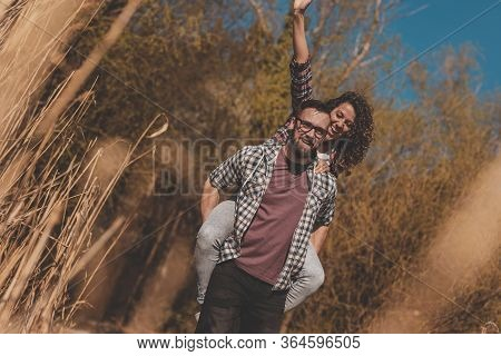 Couple In Love Having Fun Outdoors, Man Piggybacking Woman While Walking On The Lake Docks And Laugh