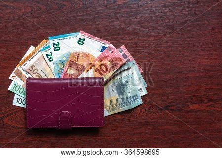 Leather Wallet With Euro Notes On Wood Background. Various Kinds Of Euro Banknotes On Desk With Leat