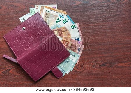 Euro Banknotes And Leather Wallet On Wood Background. Leather Wallet And Various Kinds Of Euro Notes