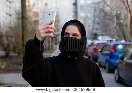 European Woman In Protective Black Mask Takes Selfie On Smartphone Outside During Coronavirus Covid-