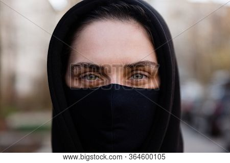Young Woman Wearing Face Mask. Handsome Woman In Black Hoodie Wear Black Medical Mask. Close Up Port