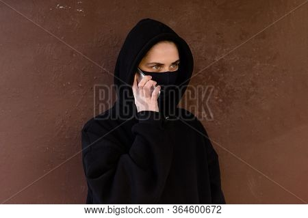 Portrait Of A Scared Girl With Hand On Chest Wearing Protective Mask Calling Doctor On Smart Phone O