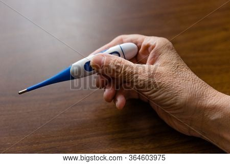 Woman With Thermometer In Her Hand Close-up