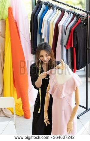 Top view of young adult asian fashion designer using measuring tape to measure dress arm at her atelier studio as sole owner. Using for entrepreneur small business startup concept.