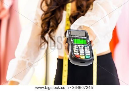 Close-up fashion designer hand hold EDC Machine for customer payment with credit card at her atelier studio as sole owner. Using for entrepreneur startup and consumerism concept.