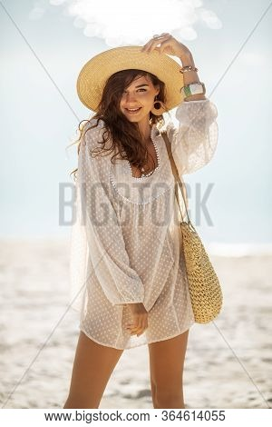 Outdoor Fashion Portrait Of Romantic Woman Standing On A Beach Against A Beautiful Sea Bokeh Backgro