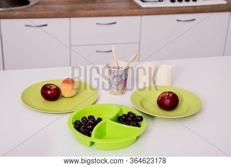 Bamboo Toothbrushes, Washcloths, Cups And Plates On The White Table In Kitchen