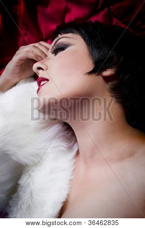seminude beautiful short haired brunette woman lying on red silk with white fur, sensuous looking