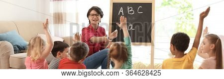 Young Nanny Teaching Little Children Indoors. Banner Design