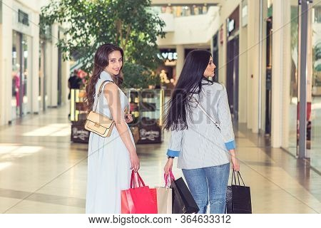Happy Two Caucasian Women Are Doing Shopping Together At The Mall Center. Two Young Women Are Walkin