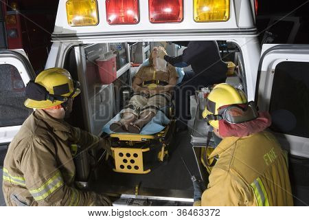 Two fireman looking at an injured person in an ambulance