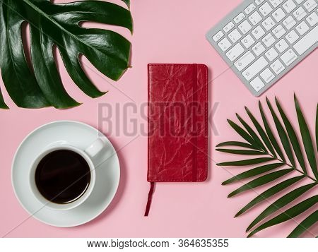 Female Workspace With Keyboard, Cup Of Black Coffee, Red Notepad Or Diary And Green Monstera And Pal