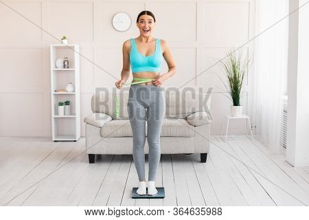 Weight Loss. Happy Woman Measuring Waist Standing On Weight-scales At Home. Empty Space For Text