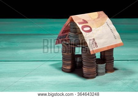 House Made Of Coins And Euro Banknote On Green Table