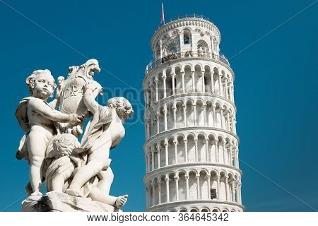 Tower Of Pisa And Statue Of Cherubs Winged Angels At Sunny Day, Italy