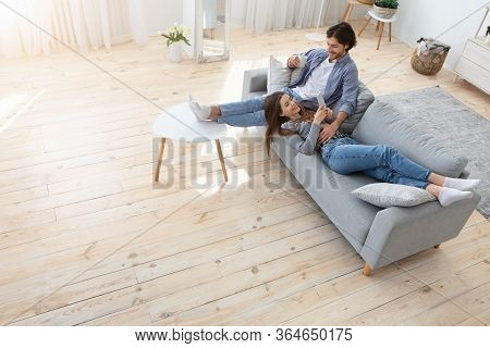 Happy Couple In Love Spending Weekend Together, Man Drinking Coffee, Woman Laying On Couch And Using