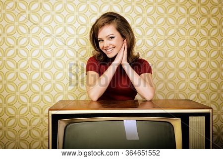 Young charming woman staing at room with vintage wallpaper and retro TV set, retro stylization 60-70s, image toned