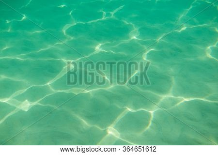 Underwater. Sun glare at the bottom of the sea. Waves underwater and rays of sunlight shining through. Deep turquoise blue sea. Ocean. Transparent water and light at sand.