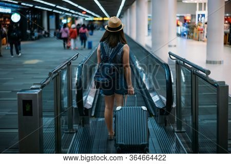 Young Woman Traveler In International Airport With Backpack Holding Suitcase Or Baggage In Her Hand,