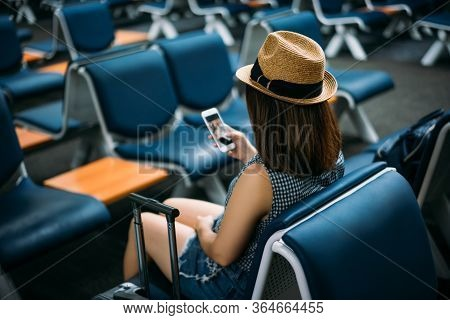 Young Woman Traveler Sitting While Using Smartphone On Chair Of Passenger In An Airport Lounge Waiti