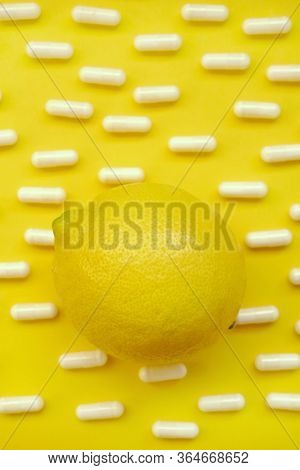Vitamin C Concept. Lemon Citrus Fruit And Medical Capsules On A Bright Yellow Background.prevention