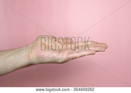 Male Hand With Fair Skin Shows A Gesture, Hand On A Light Pink Background. Open Palm Outstretched, S