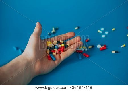 A Bunch Of Different Pills In A Mans Hand On A Blue Background