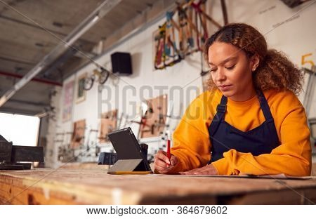 Female Craftsperson In Carpentry Workshop For Bamboo Bicycles Using Digital Tablet