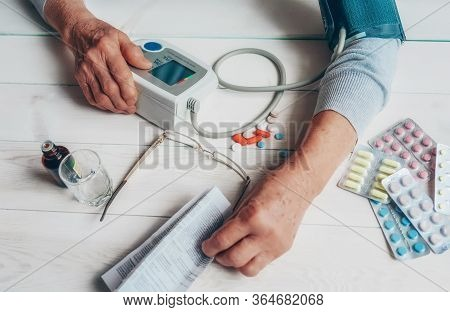 Senior Wrinkled Hand Pushing Back Pills And Thermometer, Dumb-bell On A Table. Another Old Woman Han