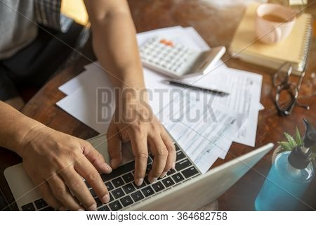 Budget And Tax Planning Concept. Accountant Is Calculating Company's Annual Tax And Typing Laptop.pe