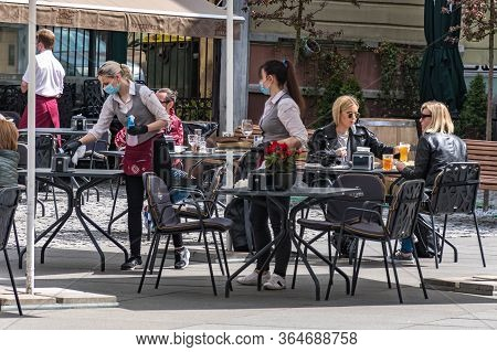 Vilnius, Lithuania - May 3 2020: Waitresses With A Mask And Gloves Disinfecting The Table Of An Outd