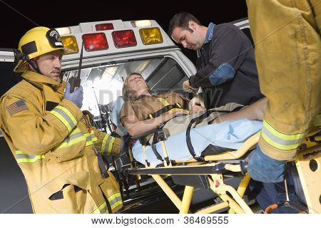 Emergency service professionals carrying patient on stretcher in ambulance