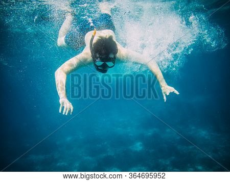 Underwater View Of A Young Diver Man Swimming Under Blue Sea Under The Surface With Snorkelling Mask