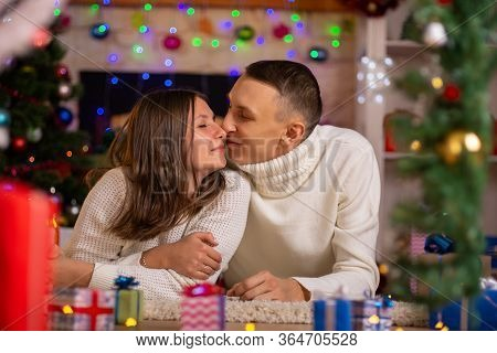 Heterosexual Couple Hugs In A Decorated Room On Christmas Day