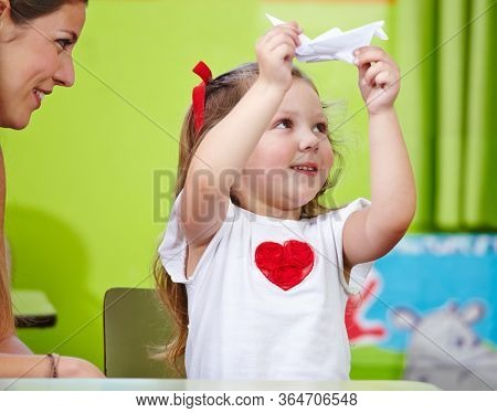 Smiling woman with girl is making origami in the nursery