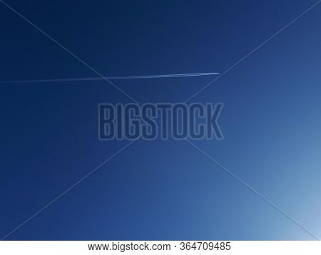 Airplane Flying In Clear Blue Sky Without The Clouds, Leaving An Inverse White Trace