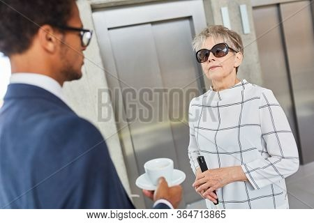 Visually impaired old woman talks to a businessman in the business office