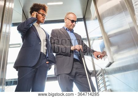 Visually impaired or blind man in the elevator presses button for inclusion concept