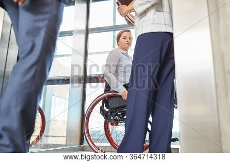 Handicapped woman in a wheelchair in the business office for inclusion concept