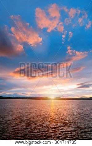 Sea sunset landscape - sea water surface lit by sunset light. Summer sunny water scene in picturesque tones.Summer sunny sea water scene in vivid colors. Sea summer nature with mountains at the horizon - panoramic sea view