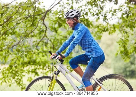 Active senior woman cycling on a cycling vacation in nature