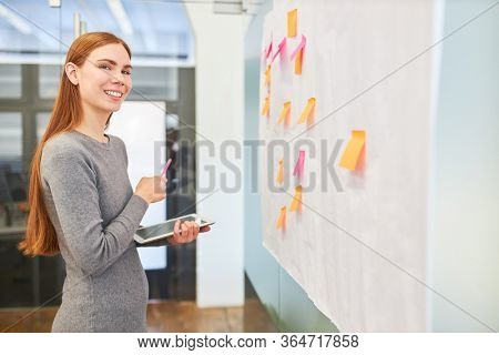 Smiling business woman or trainee in brainstorming workshop with sticky notes