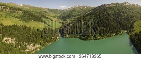 Aerial panorama of Lac de Roselend in the Savoie Alps in summer